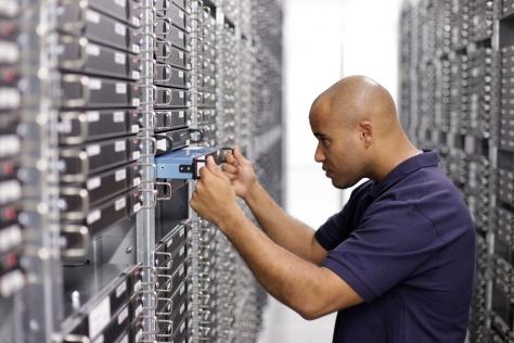 An engineer maintaining a 1U server.